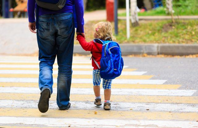 father walking young daughter with backpack