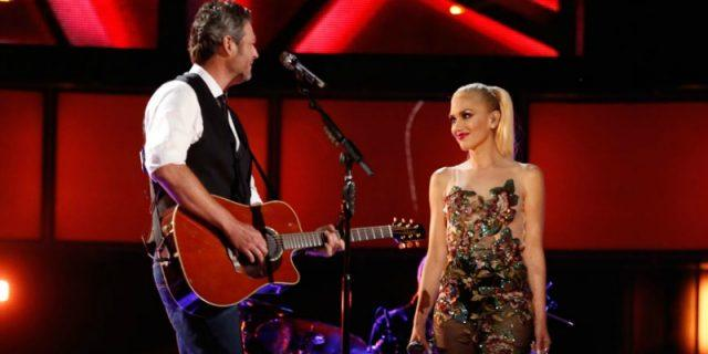 Blake Shelton and Gwen Stefani standing with each other as they perform on stage.
