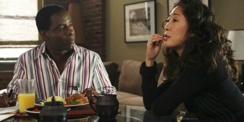 Burke and Cristina sitting at a table over breakfast