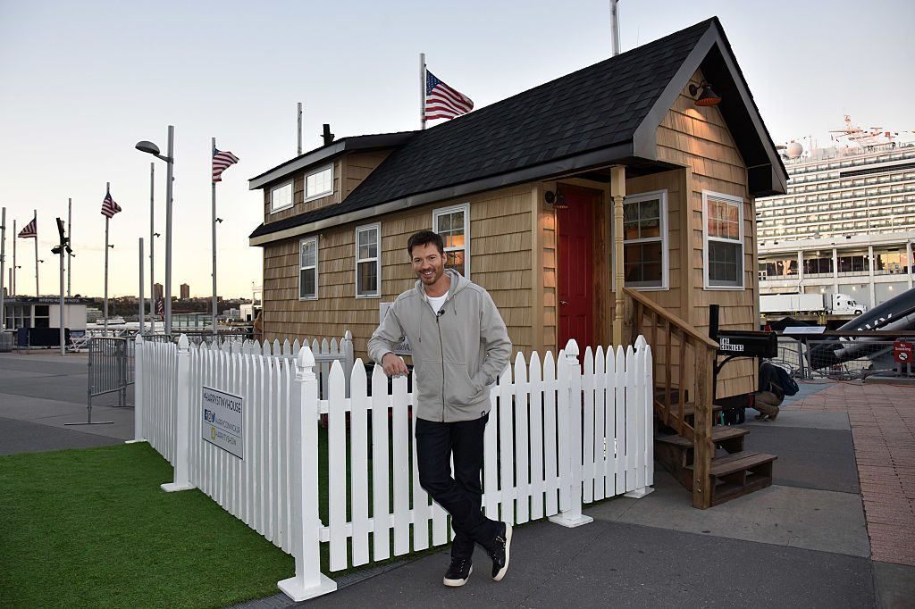 Singer and actor Harry Connick Jr. poses in front of a tiny house.