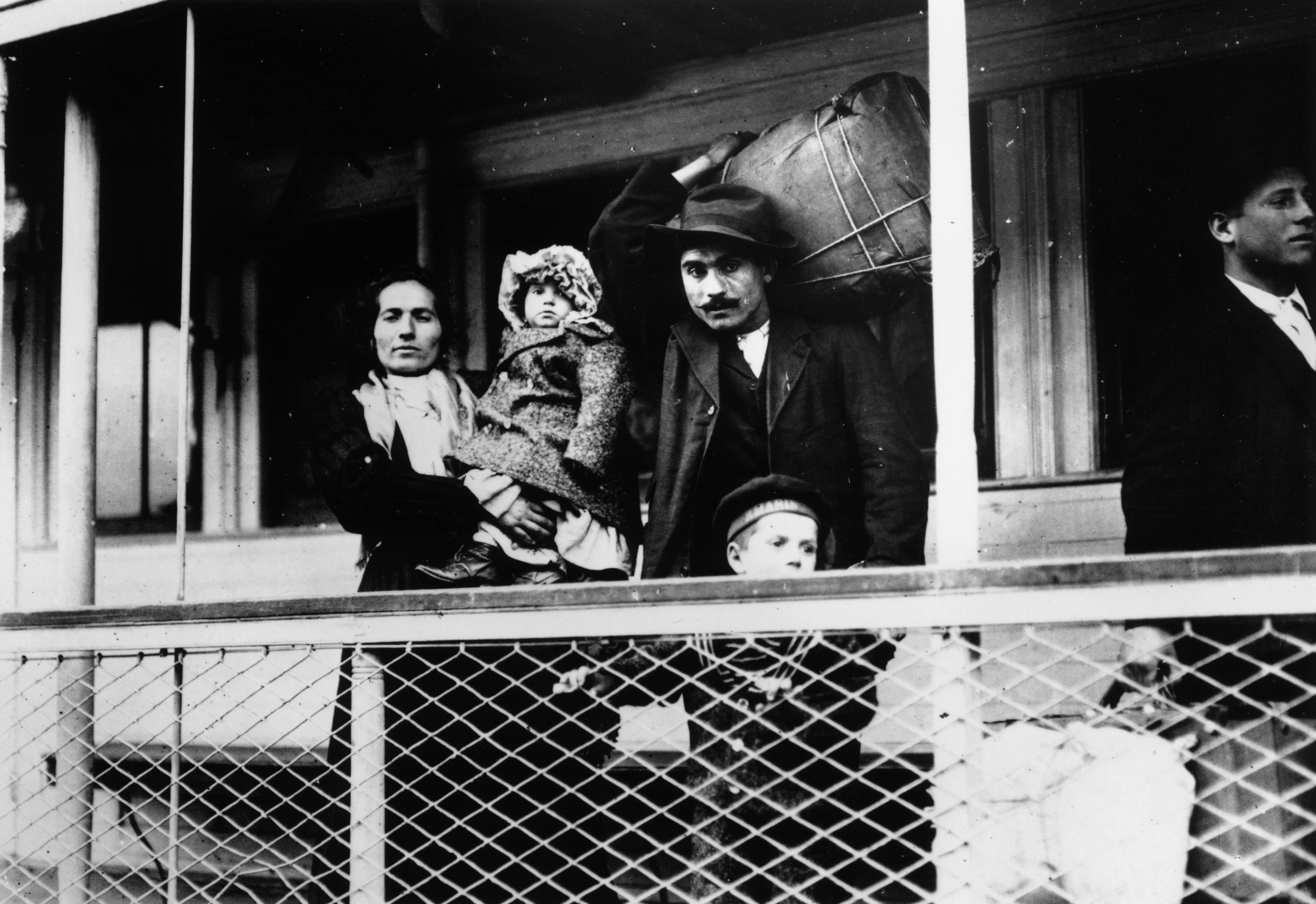 Italian immigrants on board a ferry from the docks to Ellis Island, New York
