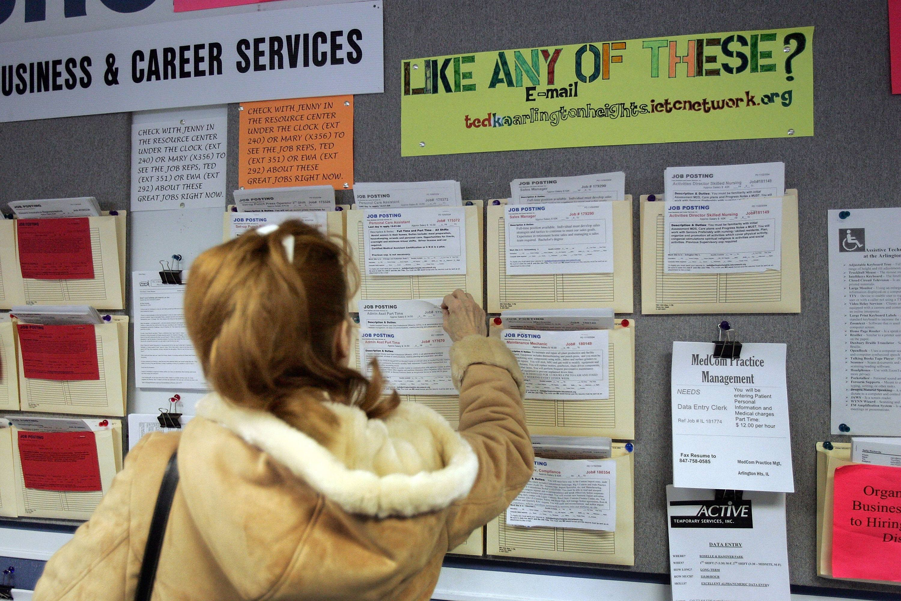 A woman looks at a board for a new job alert