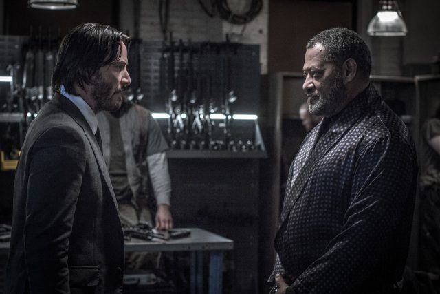 John Wick speaking to a man in a room full of weapons.