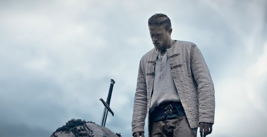 Charlie Hunnam stands next to the Excalibur sword in King Arthur: Legend of the Sword