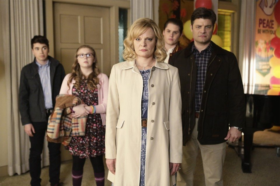 The cast of the Real O'Neals stand in front of a door in formation
