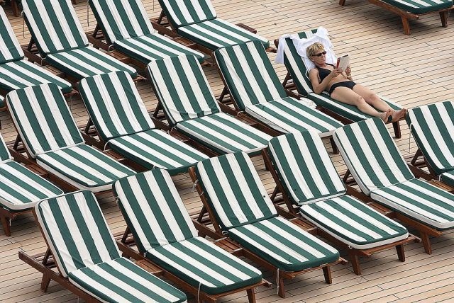 cruise passenger sitting in pool chair