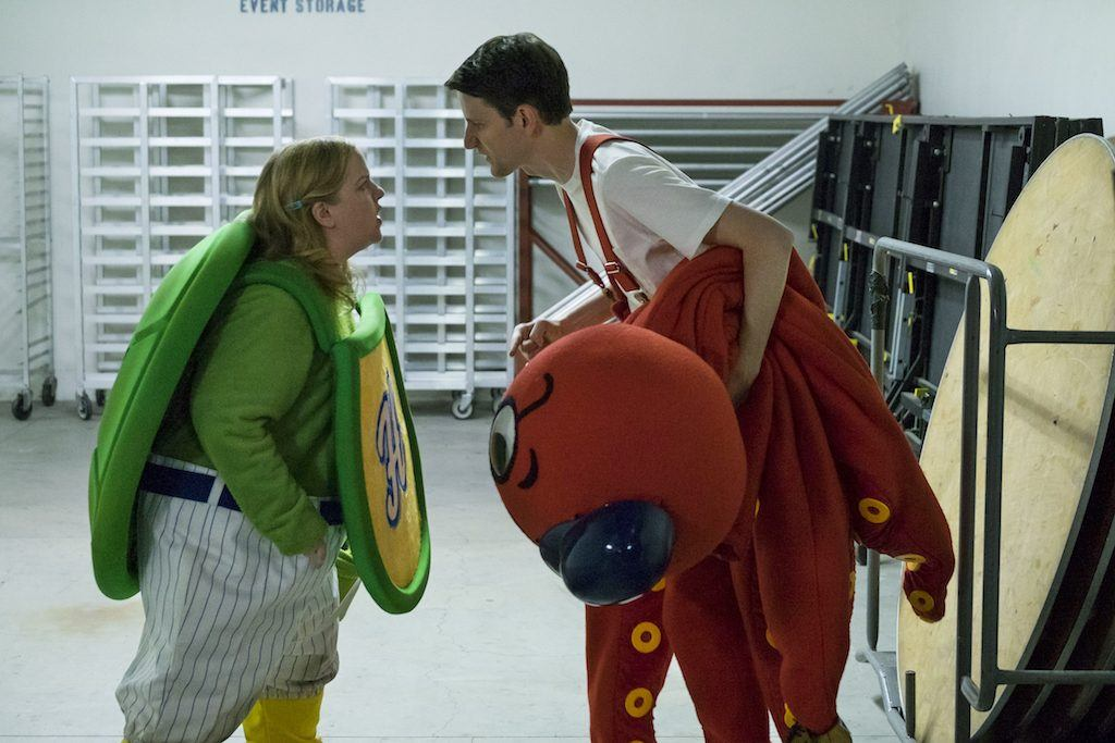 A woman in a green costume and a man in a red one yell at one another