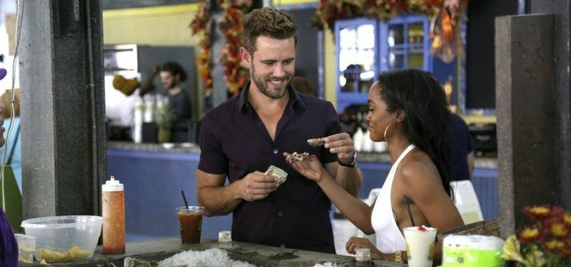 Rachel Lindsay and Nick Viall are holding food in The Bachelor.