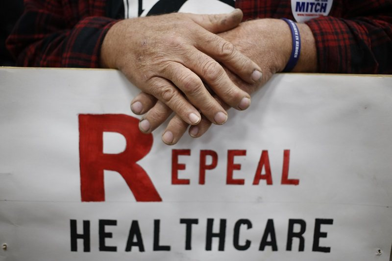 A Mitch McConnell supporter holds a sign calling for the repeal of Obamacare during a rally.