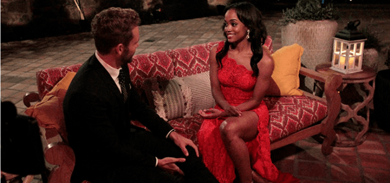 The Bachelor's Rachel Lindsey sits on a couch and talks to the bachelor, Nick