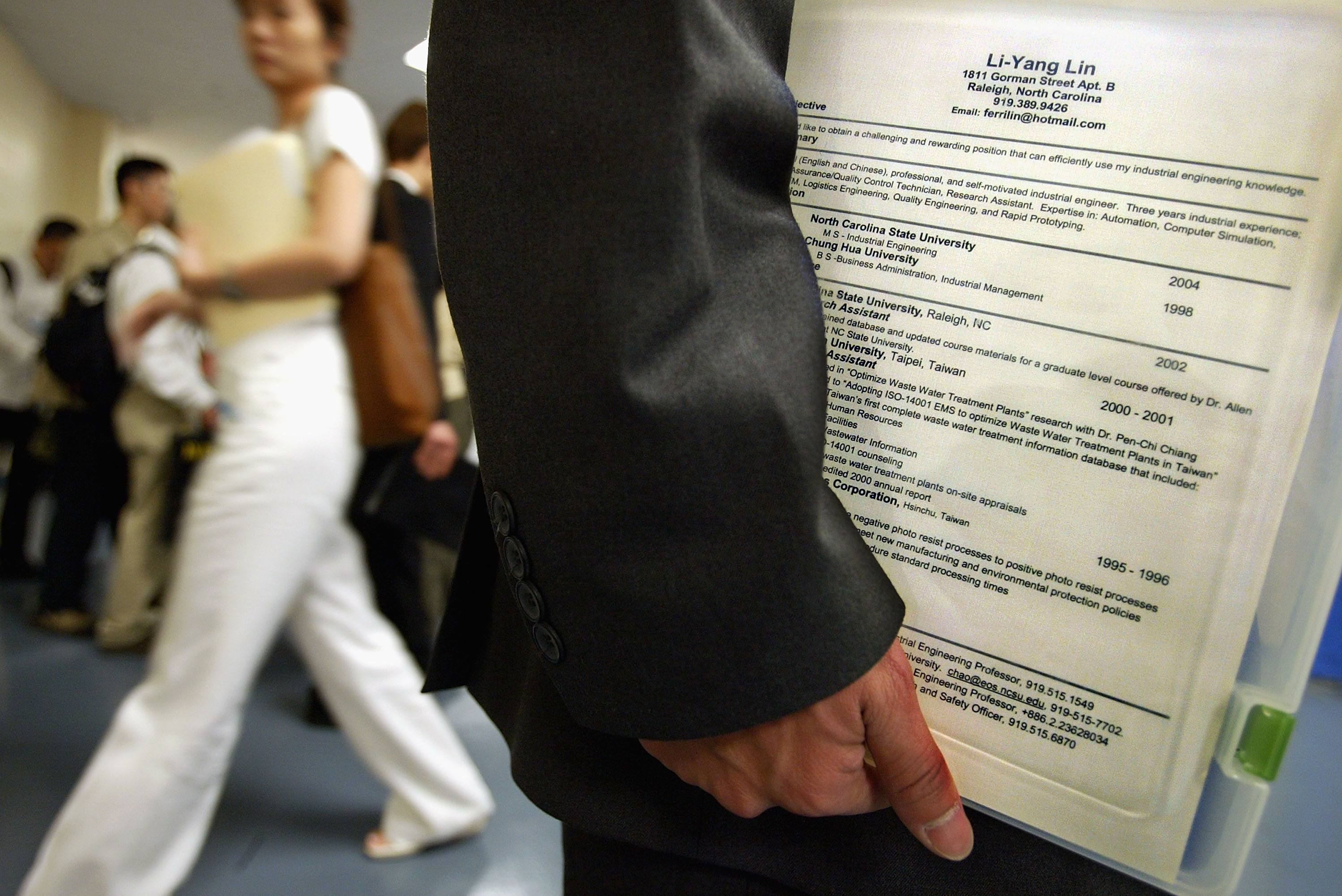 A man holds his buzzword-heavy resume at a job fair