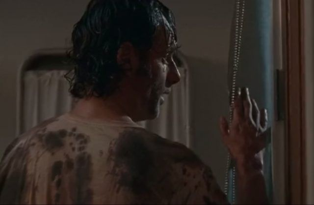 Rick stands in front of a window while wearing a blood-drenched shirt.