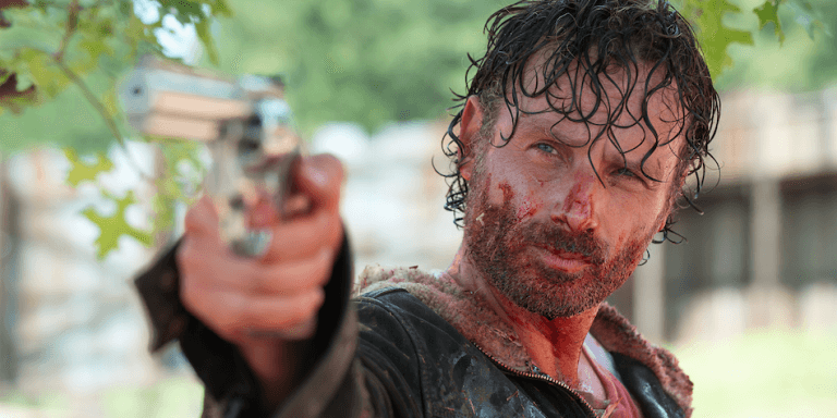 Andrew Lincoln's Rick Grimes with blood on his face points a gun underneath a tree in AMC's The Walking Dead