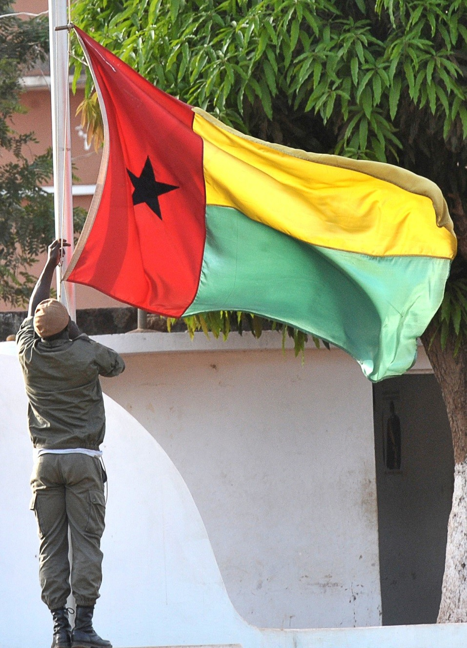 A soldier of Guinea-Bissau lowers the flag