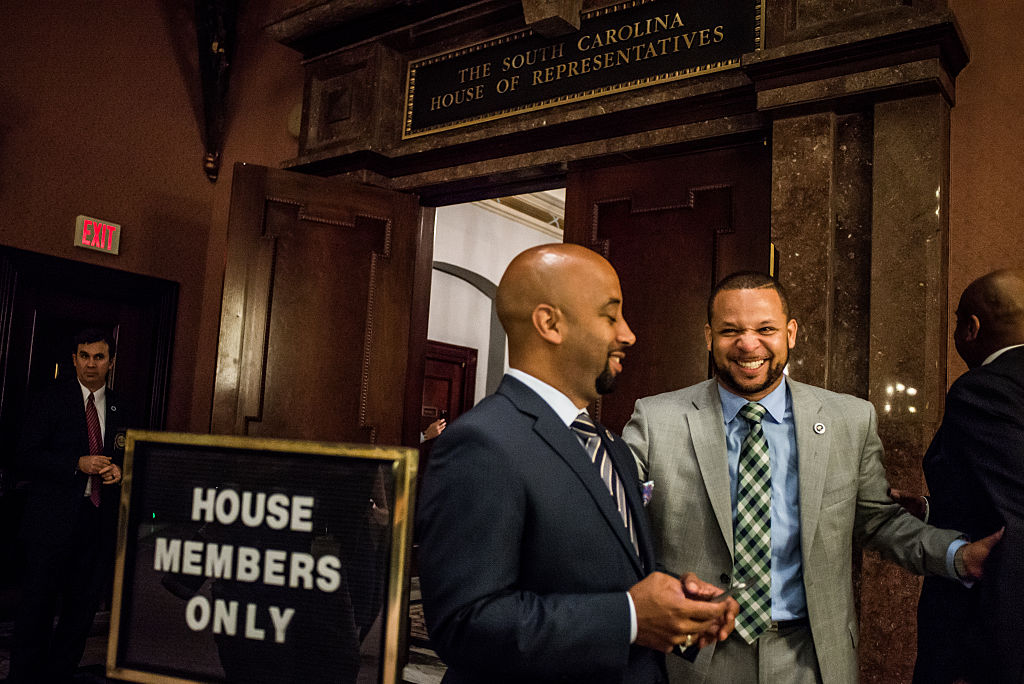 State Reps. Cezar McKnight and John King share a laugh between bill readings at the statehouse in Columbia, South Carolina.