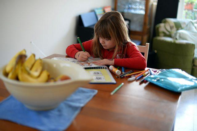 child coloring at the kitchen table