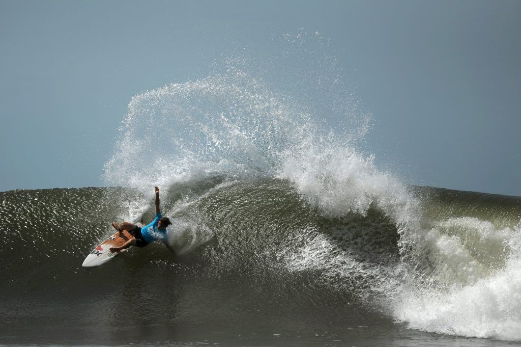 A man rides a wave on his surfboard in El Salvador
