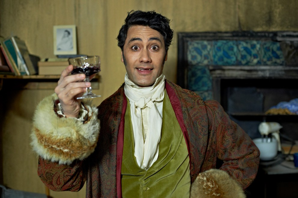 Taika Waititi smiling and holding a glass of wine in What We Do In the Shadows