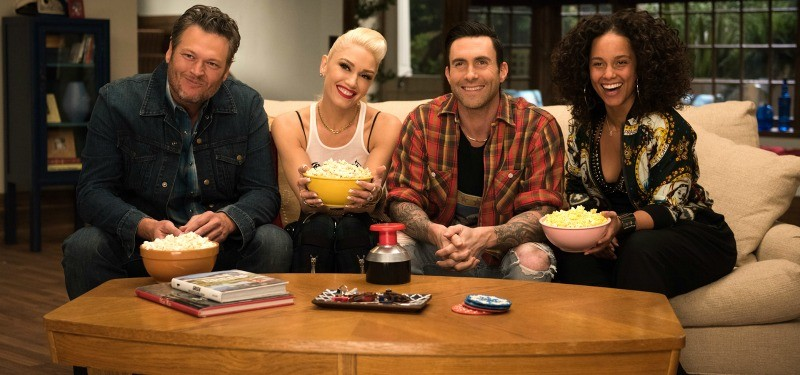 Blake Shelton, Gwen Stefani, Adam Levine, and Alicia Keys sitting on a coach holding bowls of popcorn.