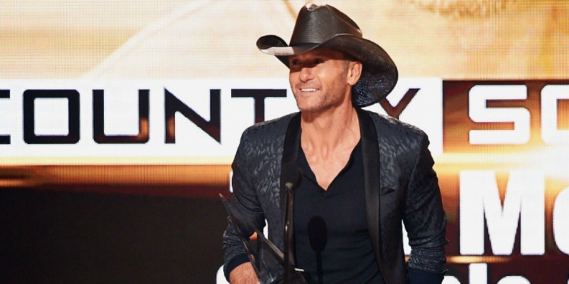 Tim McGraw is on stage holding an award.