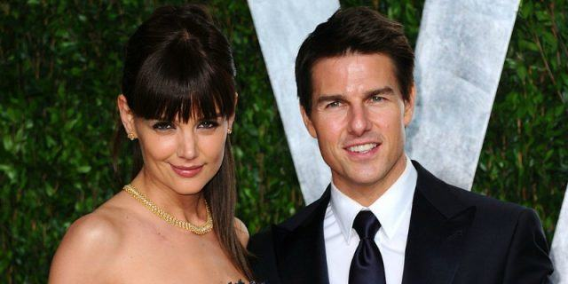 Katie Holmes and Tom Cruise posing for photos together at a formal event.