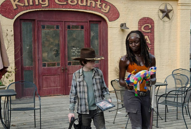 Michonne walking with Carl and holding a rainbow cat statue in 'The Walking Dead' episode 'Clear'