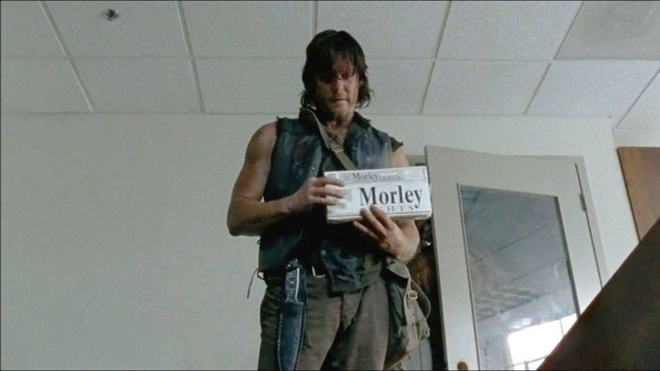 "Daryl is standing in a room holding up something that says ""Morley."""