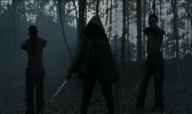 Michonne, in a hood, wielding her katana, stands in the shadows with her pet zombies in 'The Walking Dead' episode 'Beside the Dying Fire'.