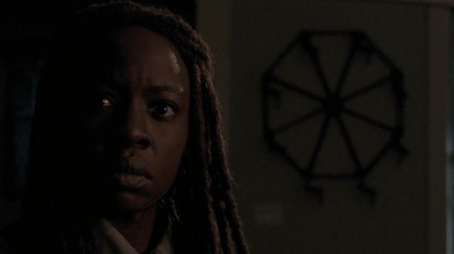 Michonne stands in front of a piece of art that looks like a wheel in 'The Walking Dead'