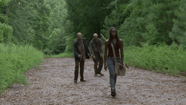 Michonne whistling as two zombies follow her in 'The Walking Dead'