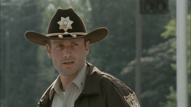 Rick Grimes, wearing a sheriff's outfit, and looking to his left.