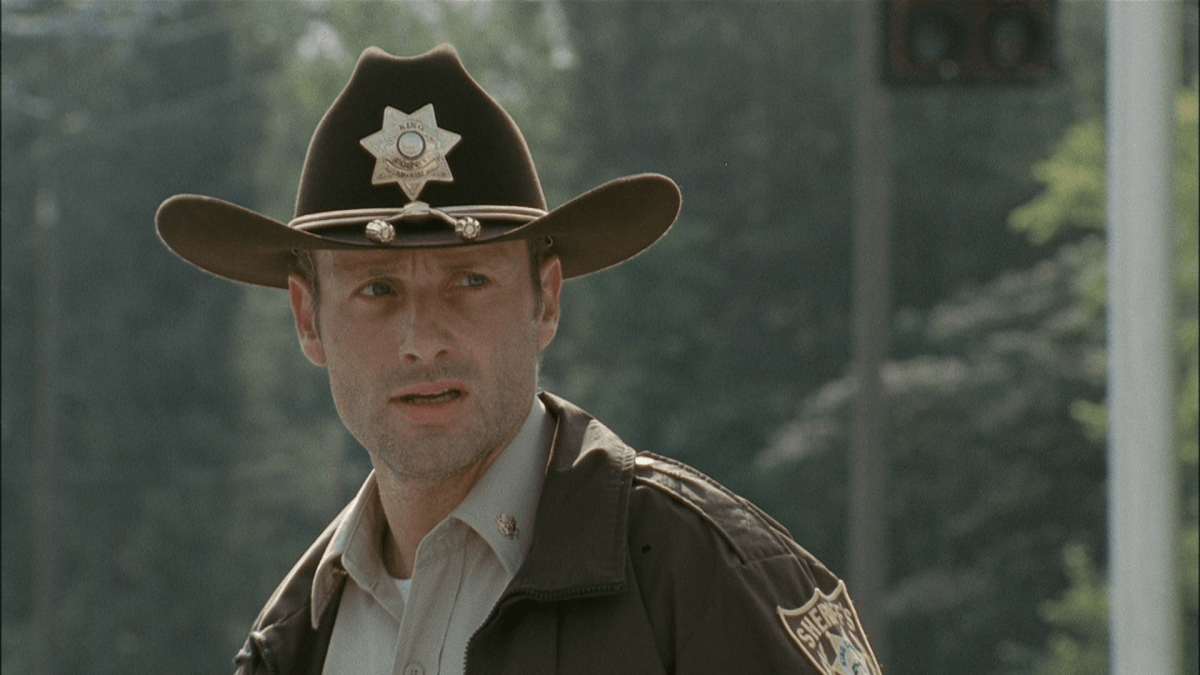 Rick Grimes, wearing a sheriff's outfit, and looking to his left