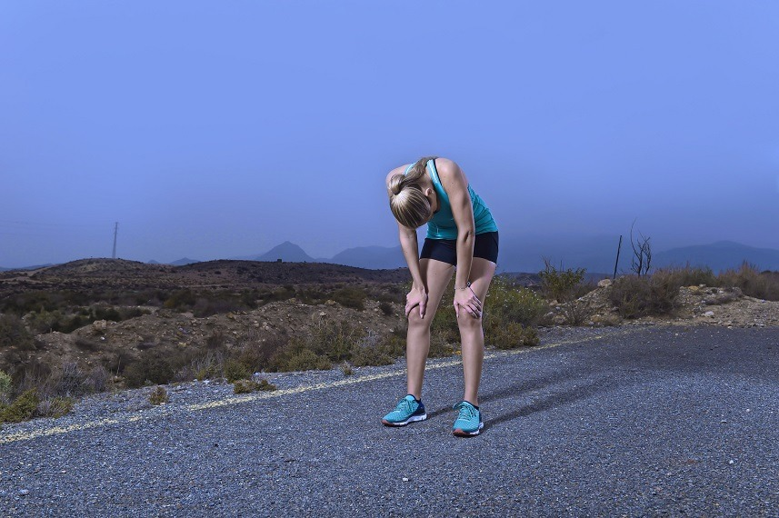 An exhausted woman stops her outdoor run to rest
