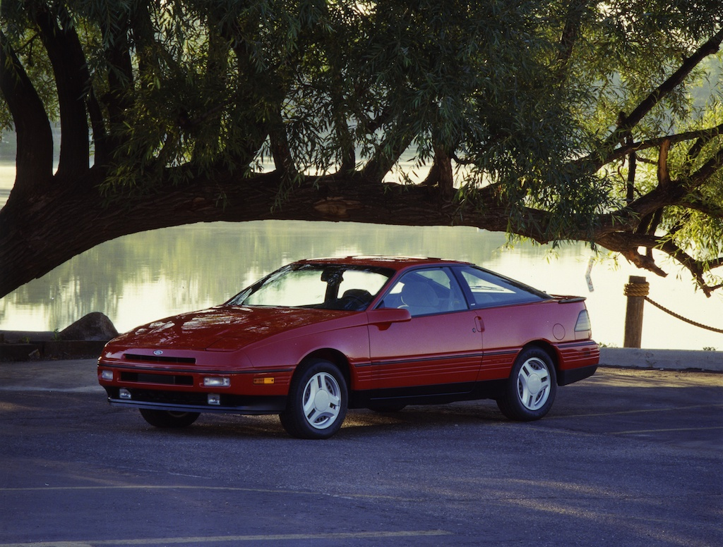 A red 1989 Ford Probe parked under a tree.