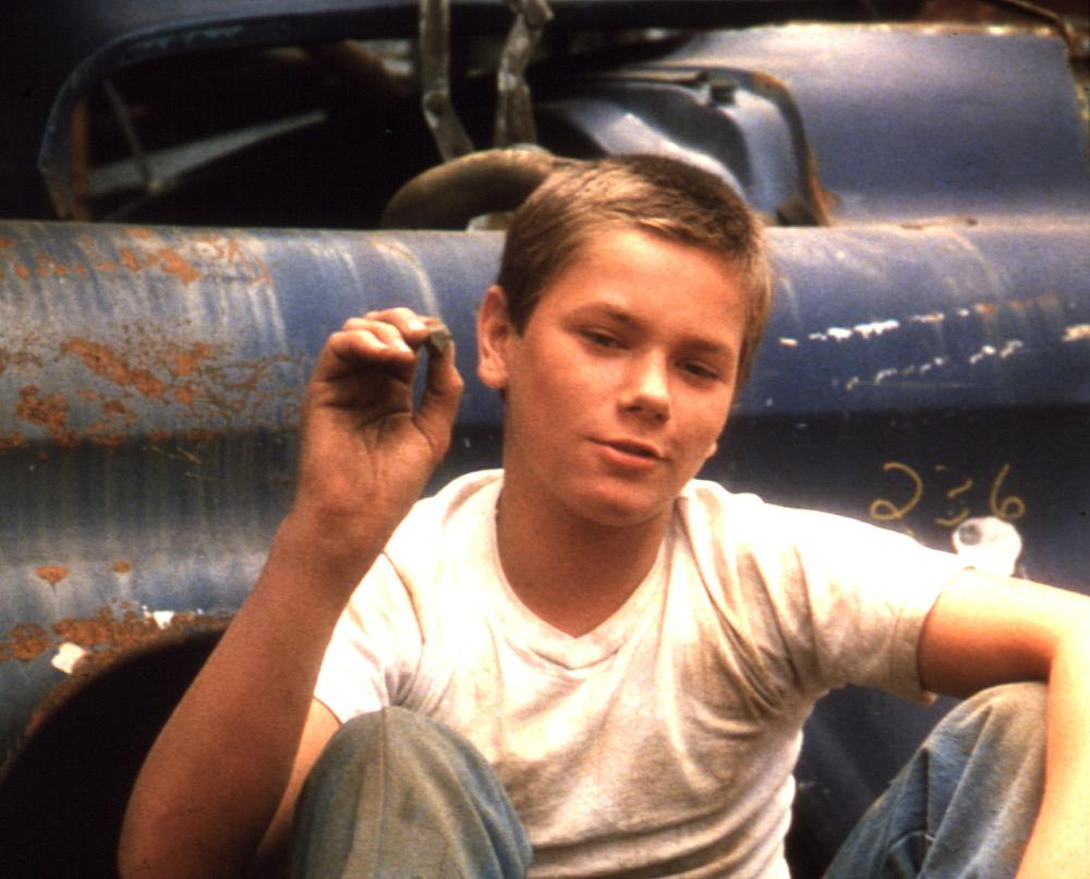 Young River Phoenix sits next to an old card in a white t-shirt in Stand by Me