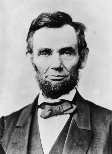 Abraham Lincoln sitting in front of a white wall.
