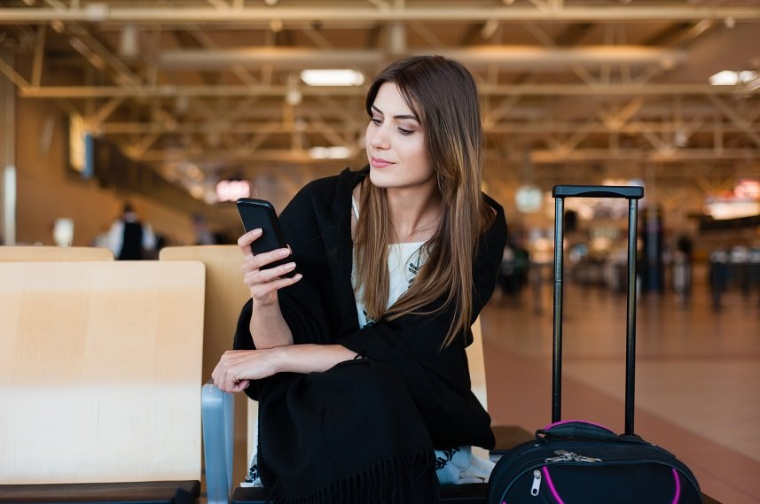 female passenger on smart phone at gate waiting in terminal