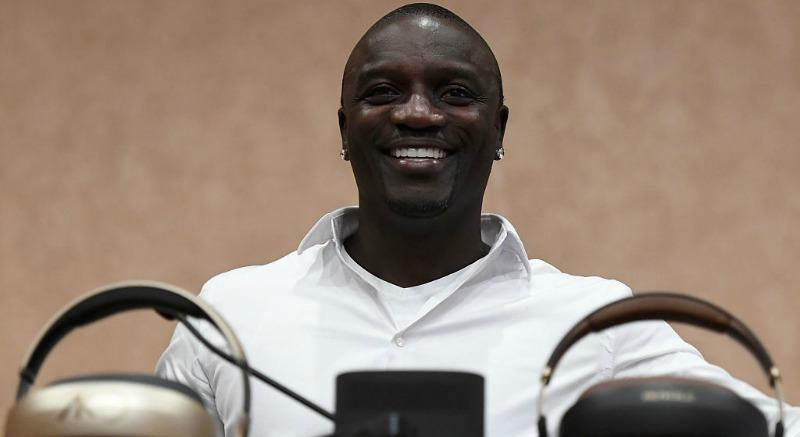 Akon is smiling as he is sitting down.