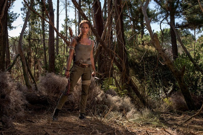 Alice Vikander's Lara Croft stands in a forest in the Tomb Raider reboot