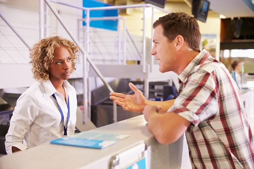 A passenger complains to an airport employee.