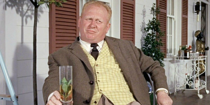Goldfinger is lounging on a chair on a porch holding a glass.