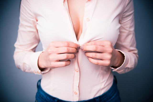 Portrait of a woman unbuttoning her shirt