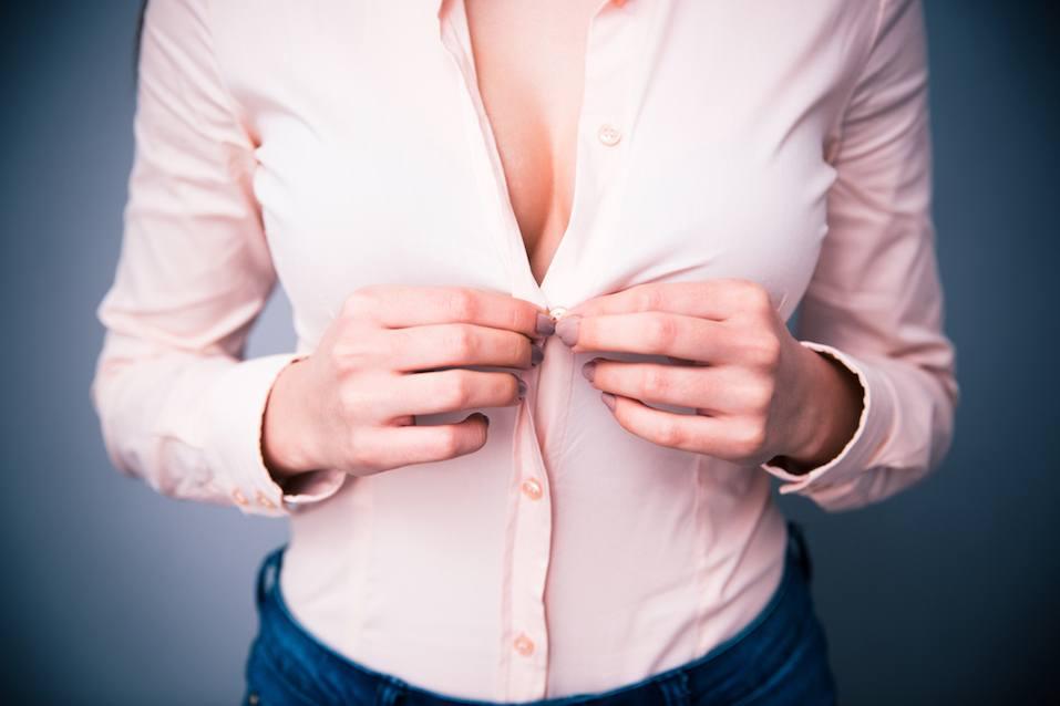 Portrait of a woman unbuttoning her shirt
