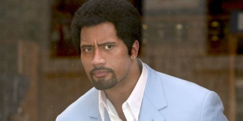 Dwayne Johnson is in a powder blue suit jacket and has an afro.