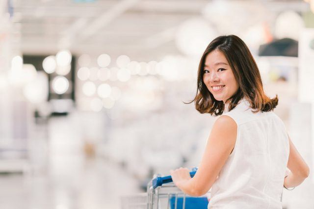 Asian woman smiling, with shopping cart