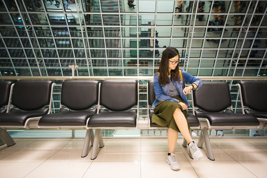 girl looking at her watch, waiting to board airplane