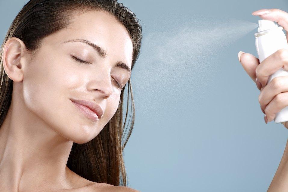 Woman applying spray water treatment