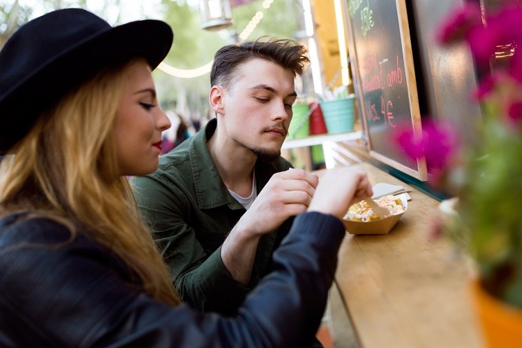 young couple at a food truck counter