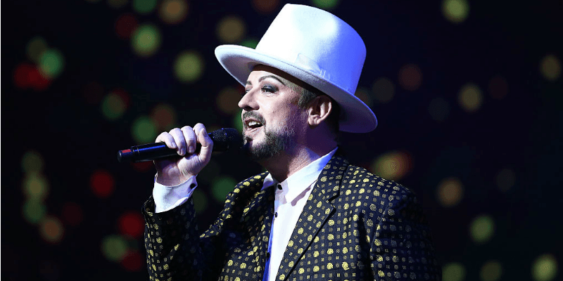 Boy George is wearing a white top hat and in a patterned jacket as he sings.