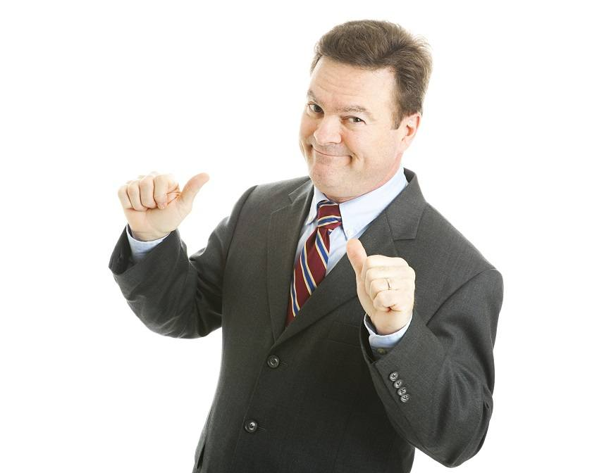 businessman points to himself with both thumbs, looking ready for a job interview